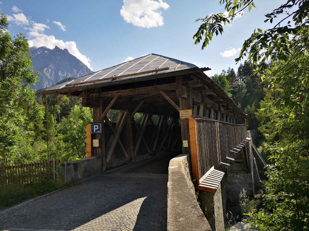 Holzbrücke führt ins Dorf